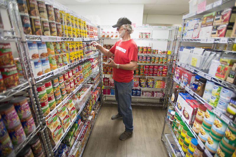 A volunteer shelving food in the food bank market