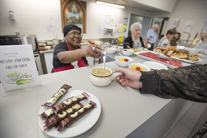 A volunteer serving food at The Compass