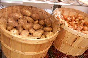 Baskets of fresh potatoes and onions