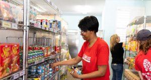 Volunteer at market shelf arranging cans of food