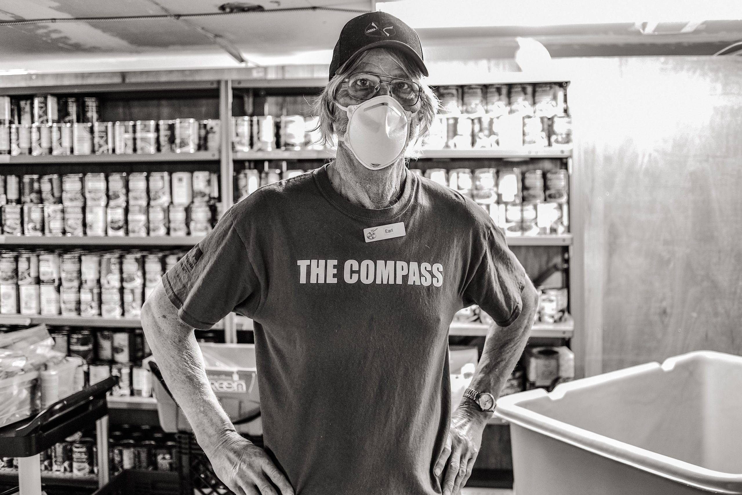 Man in a mask working at The Compass foodbank