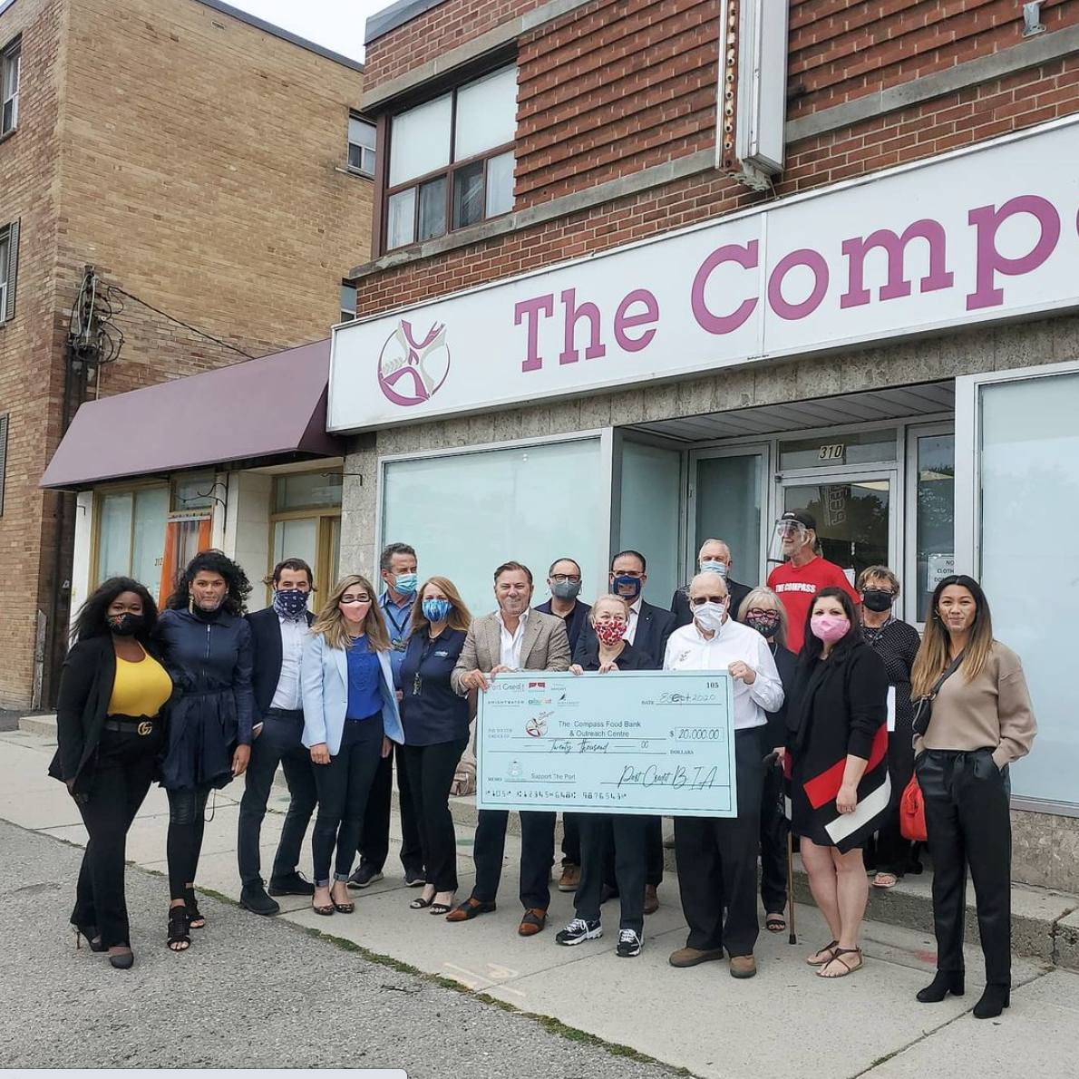 People standing in front of The Compass building with large cheque